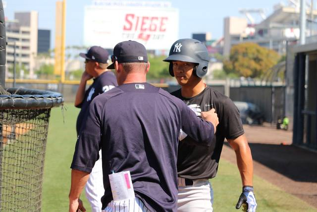 Scranton/Wilkes-Barre RailRiders catcher Chace Numata receives advice from a coach during batting practice prior to Sunday's spring training game against the Buffalo Bisons at the New York Yankees minor league complex in Tampa, Fla.