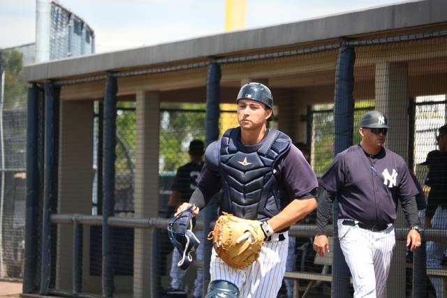 Scranton/Wilkes-Barre RailRiders catcher Kyle Higashioka heads back onto the field during Sunday's spring training game against the Buffalo Bisons at the New York Yankees minor league complex in Tampa, Fla.