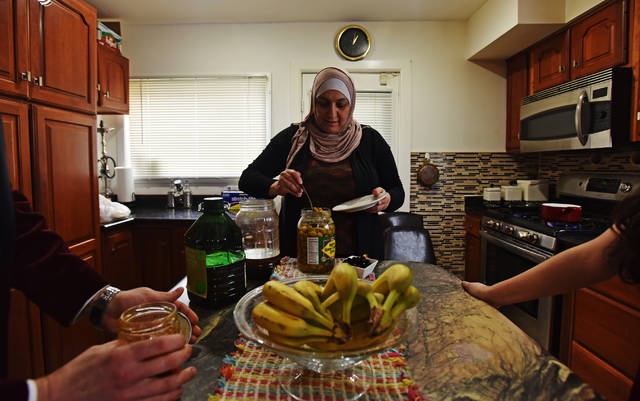 Khitam Zamel prepares breakfast with her family in her Kingston home on a recent Saturday.