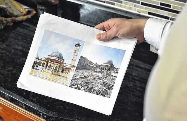 Anas Allouz holds up photos from his native Syria showing a comparison of how a building used to look versus how it looks now after seven years of fighting in the Syrian civil war.
