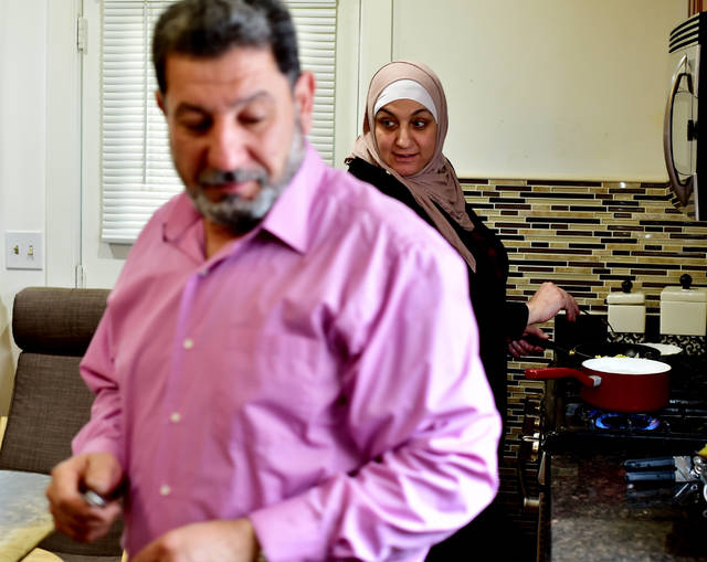 Mother of the family Khitam Zamel prepares breakfast with help from husband Turki Allouz in their Kingston home. Zamel kept her maiden name after marriage, which is not uncommon in the Arab world.