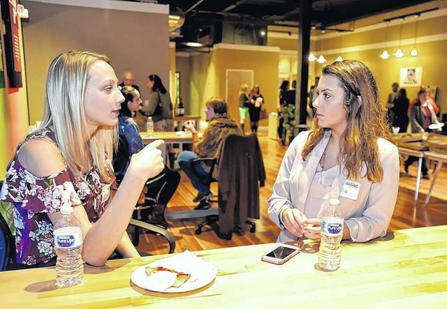 Jessica Bienkowski, of FASTSIGNS, left, talks with Wilkes student Julia Jonelunas, 20, at the Chamber's Connect Spotlight Series event Thursday in Wilkes-Barre.