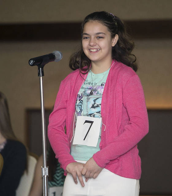 Jevahnie Hernandez, 10, of Heights-Murray Elementary School, smiles to the judges and crowd after spelling her first word correctly.