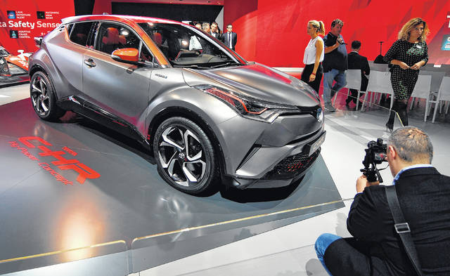 A man films a Toyota C-HR concept on the first media day of the International Frankfurt Motor Show IAA in Frankfurt, Germany.