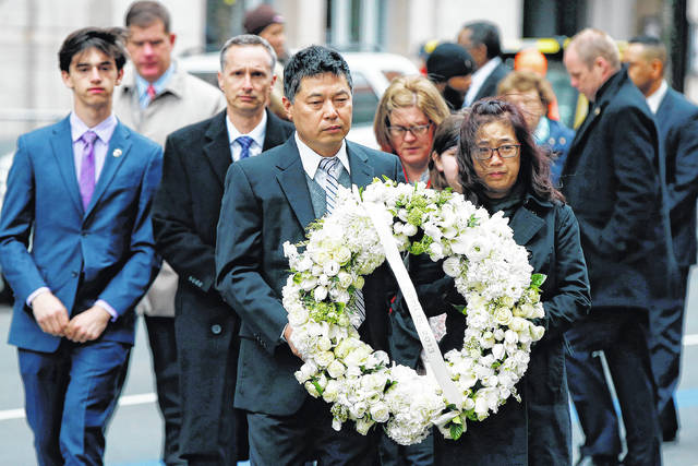 The father of Lingzi Lu, Jun Lu, foreground left, and her aunt Helen Zhao, foreground right, carry a wreath ahead of the family of Martin Richard, background from left, Henry, Bill, Denise and Jane, partially hidden, during a ceremony at the site where Martin Richard and Lingzi Lu were killed in the second explosion at the 2013 Boston Marathon on Sunday in Boston.