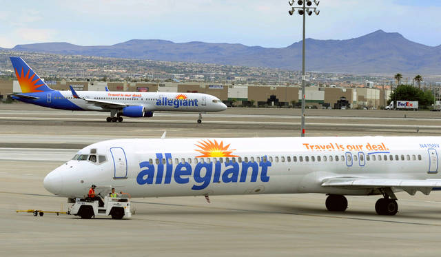 """File - In this May 9, 2013, file photo, two Allegiant Air jets taxi at McCarran International Airport in Las Vegas. Shares of Allegiant Air's parent company are tumbling in Monday, April 16, 2018, premarket trading following a """"60 Minutes"""" investigation that expressed serious safety concerns about the airline."""