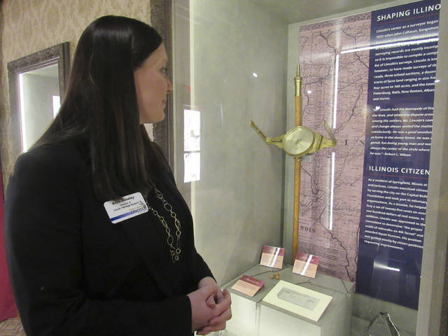 Anne Moseley, director of the Lincoln Heritage Museum at Lincoln College, looks over a new exhibit, 'Let Us Do Our Duty,' that includes surveying equipment like Abraham Lincoln would have used, in Lincoln, Ill. This part of the exhibit also includes a pay stub from his time as state representative: $100 for a full term. With a new director and a new exhibit that's part of Illinois' bicentennial celebration, the museum is emphasizing the importance of citizenship and responsibility. The new exhibit will remain open through December.