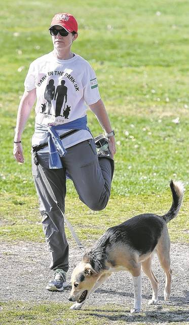 Fran Martin, Hanover Twp., stretches a bit before her and pooch Auggie, a three-yr. mix, get ready for the Bark at the Park 5K race at Kirby Park on Saturday morning sponsored by Jr. Leadership Wilkes-Barre to benefit the local SPCA. Tony Callaio | For Times Leader