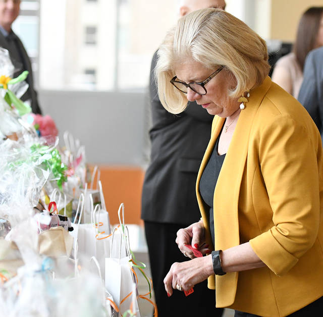 Cornelia 'Corny' Romanowski, Shavertown, a volunteer with 'Dinners for Kids,' looks over raffle items prior to a dinner to honor Bill Jones, of the United Way of Wyoming Valley, and Lynn Evans Biga, of Luzerne County Head Start, on Wednesday at Misercorida University's Insalaco Hall.