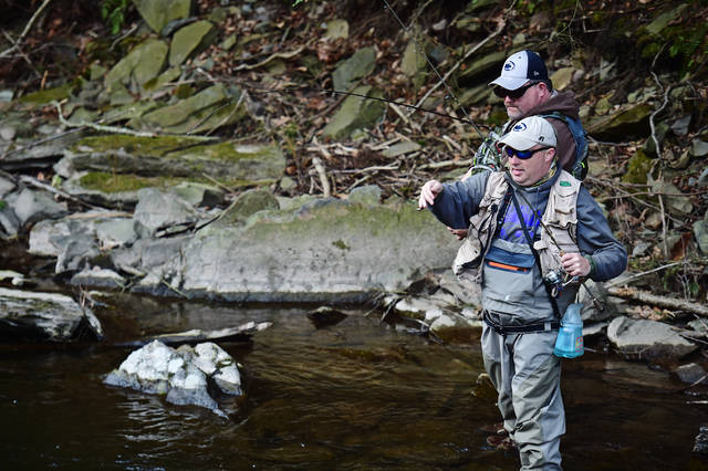 Luther Snyder (front), of Duryea, fishes in Harveys Creek with brother John Snyder, of Loganton, on the opening day of trout season Saturday.