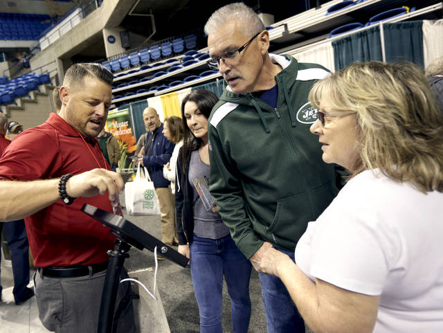 SquareDecko president Marc Lussier, left, describes products to Mary Kate Coulter and her parents, John and Dorothy Coulter, all of Mountain Top, during the final day of the Home and Garden Show at Mohegan Sun Arena on Sunday.