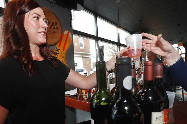 Amy Niemkiewicz, senior sales executive for Nawrocki Imports, hands out a sample of wine Sunday at Senunas Bar & Grill.
