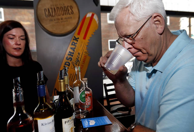 Jim Powell checks out a wine during a fundraiser at Senunas' Bar & Grill in Wilkes-Barre on Sunday.