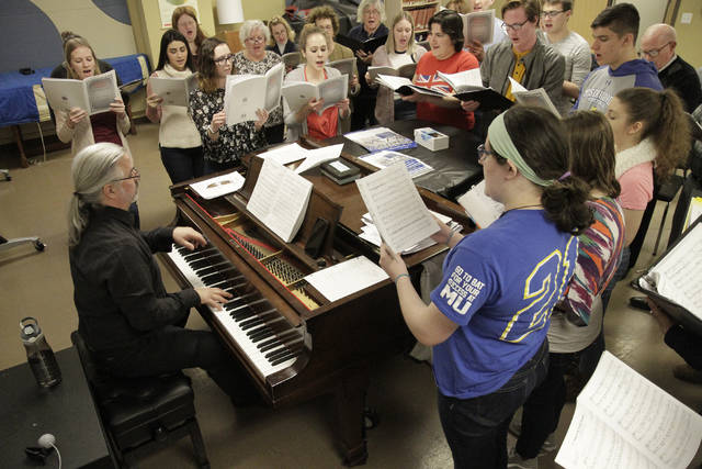 The Community Choir at Misericordia University gathers around the piano as conductor Matthew Rupcich plays music from the 'Holocaust Cantata,' set to be performed April 26 on campus.