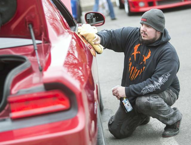 Nick Kohler, of Montrose, cleans his 2011 Dodge Challenger themed after the comic book character Deadpool at Wilkes University's branch of the American Society of Mechanical Engineers' annual car show Sunday.
