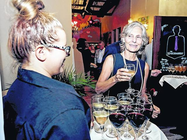 CASA of Luzerne County volunteer Ann Brado, of Shavertown, right, selects a glass of champagne from Westmoreland Club server Shawna Protchko at 'An Evening in CASAblanca' fundraiser at The Room at 900 in Forty Fort on Thursday. Bill Tarutis | For Times Leader