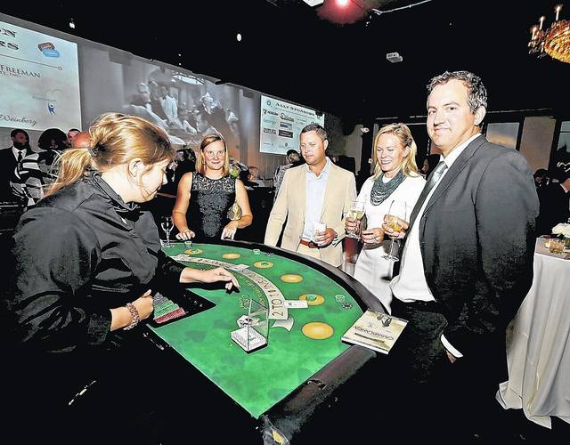 Steve Maakestad, of Dallas, right, Katherine and Ryan Flood, of Mountain Top, and Tiffany Maakestad, of Dallas, are dealt their cards from blackjack dealer Hayley Blumer at the CASAblanca event Thursday in Forty Fort. Bill Tarutis | For Times Leader
