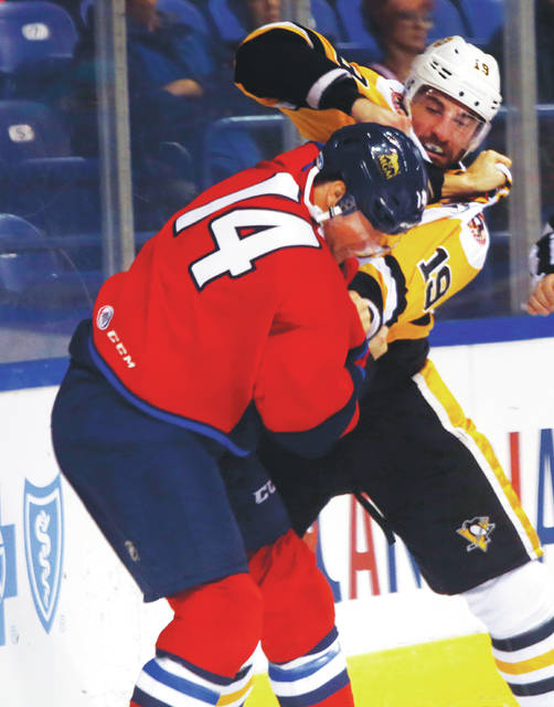Penguins captain Garrett Wilson exchanges blows with Springfield  8217 s  Joel Lowry behind the 33c4f20df