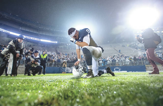Penn State quarterback Trace McSorley kneels down in the end zone before  kissing the grass and 8891ff103