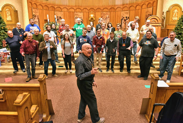 Phil Brown, of Shavertown, co-director of the Wyoming Valley Barbershop Harmony Chorus, leads the group during a rehearsal for the 'Love at Christmas' concert, which is set for 2 p.m. Sunday at Sts. Peter and Paul Church in Plains. Sean McKeag | For Times Leader