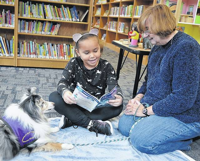 Angie, a 9-year-old therapy dog, listens to Cecilia Coolbaugh, 7, of West Pittston, as Helene Skopek-Krygier looks on at the Pittston Memorial Library on Saturday. Skopek-Krygier is president of Pleasure of Your Company Therapy Dogs, which runs a Furry Tails Reading Partners program at area libraries. Tony Callaio | For Times Leader
