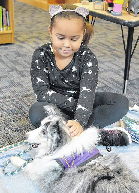 Cecilia Coolbaugh, 7, of West Pittston, pets therapy dog Angie at the Pittston Memorial Library on Saturday during a Furry Tails Reading Partners event. Angie serves as the listener while younger children sharpen their reading skills. Tony Callaio | For Times Leader