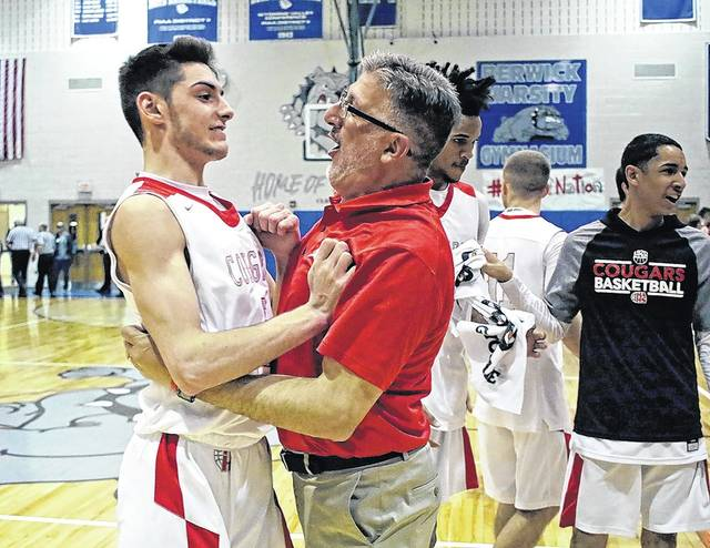 Hazleton Area head coach Mike Joseph hugs point guard Andrew Vayda after the Cougars defeated Crestwood, 54-43 in overtime to win the WVC Division 1 boys basketball championship at Berwick Middle School on Wednesday night. Bill Tarutis | For Times Leader