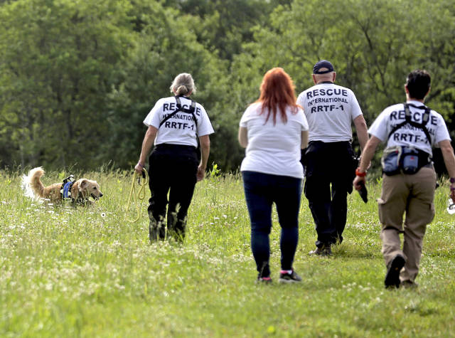Family friend Judy Lorah Fisher, second from left, follows members of Rescue International during a K9 search for the remains of Phylicia Thomas in a field along Timber Lane in Hunlock Creek last June. Times Leader file photo