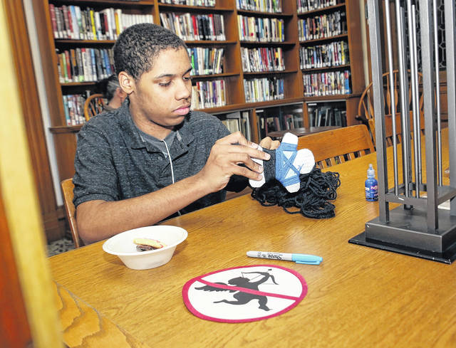 The 'voodoo doll' part of the Teen Night anti-Valentine party at the Osterhout Free Library on Wednesday evening was all in fun, as 14-year-old Jaair Lowry, of Kingston, proved by decorating a doll to look like a YouTube gamer he admires. Amanda Hrycyna | For Times Leader