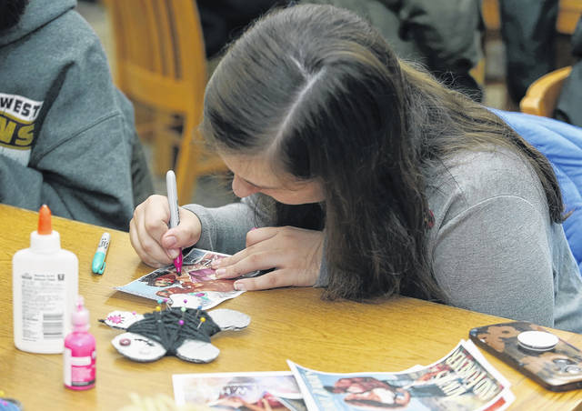 'I'm making them both pirates,' Helen Campbell, 18, of Wilkes-Barre, said as she added eye patches and a parrot to a downloaded picture of a romance novel cover during the Osterhout Free Library's Teen Night on Wednesday, which featured an anti-Valentine theme. Amanda Hrycyna | For Times Leader