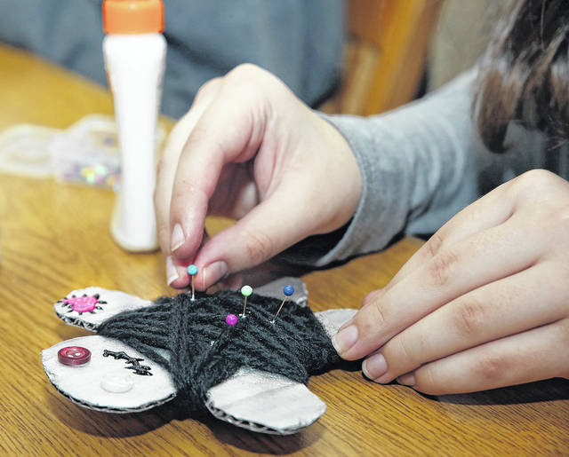 Helen Campbell, 18, of Wilkes-Barre, for years a faithful participant in Osterhout Free Library Teen Night activities, adds pins to the 'voodoo doll' she crafted during the teen group's anti-Valentine party Wednesday. Amanda Hrycyna | For Times Leader