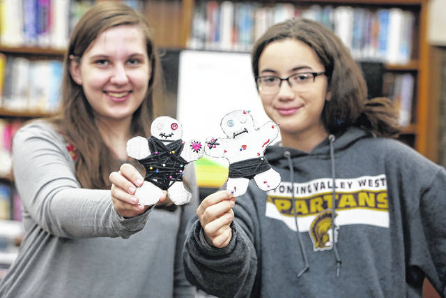 Helen Campbell, 18, of Wilkes-Barre, left, and Skyler Stempien, 13, of Plymoth, hold up the anti-Valentine voodoo dolls they made 'just for fun' Wednesday at the Osterhout Free Library's Teen Night. Amanda Hrycyna | For Times Leader