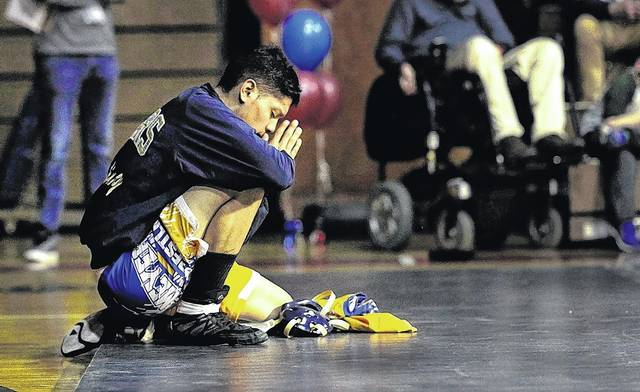 Meyers wrestler Rafael Olmedo kneels on the edge of the mat, praying for Coughlin's Tyler Faust, who was injuried in the 152-pound bout Wednesday at Coughlin High School in Wilkes-Barre. Fred Adams | For Times Leader