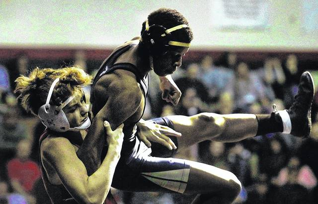 Coughlin's Nino Cinti picks up Meyers' Andre Robinson from the mat during the 132-pound bout Wednesday at Coughlin High School in Wilkes-Barre. Cinti later pinned Robinson to win the bout. Fred Adams | For Times Leader