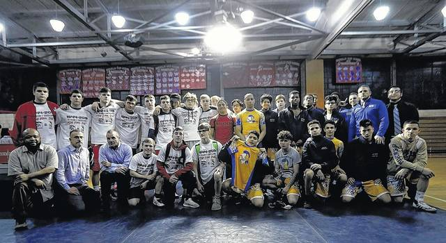 The Coughlin and Meyers wrestling teams get together for a photo after one final dual. The schools will merge with GAR next season to form the Wilkes-Barre Area Wolfpack. Fred Adams | For Times Leader