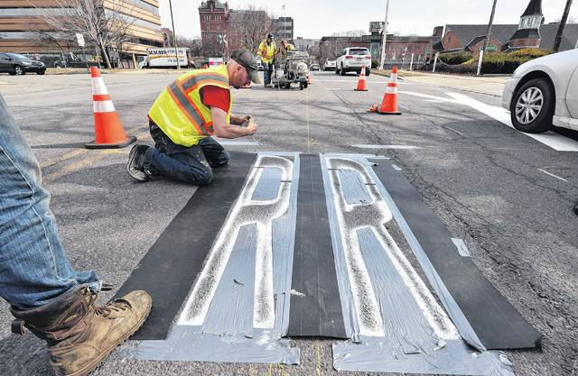 Andy Balant applies tape for a railroad crossing sign to be painted on East Market Street Thursday afternoon. Workers from Mayo Striping were updating lines and signs on the roadway as part of a project to improve crossing safety. Aimee Dilger | Times Leader