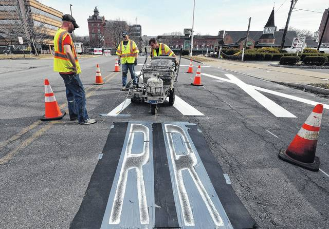 Andy Balant, Mike Niedzwiecki and Joe Lenchick paint railroad crossing markings on East Market Street Thursday afternoon. Aimee Dilger | Times Leader
