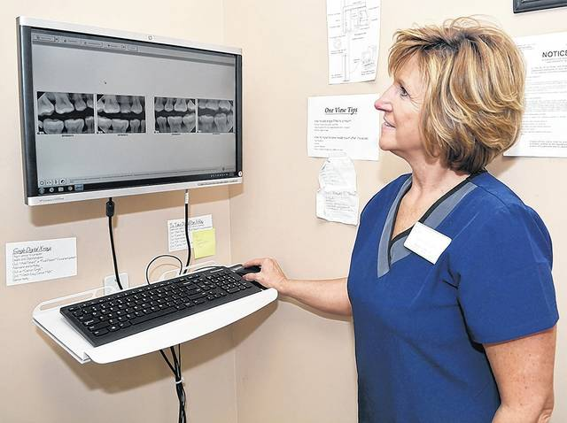 Darcie Schaffer, Volunteers in Medicine manager of dental services, looks over X-rays at the dental clinic at 190 N. Pennsylvania Ave., Wilkes-Barre. She's helping plan a free dental clinic for area residents this summer. Tony Callaio | For Times Leader
