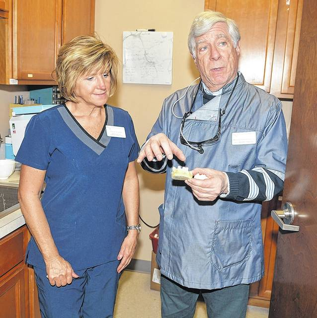 Darcie Schaffer, Volunteers in Medicine manager of dental services, and Richard Grossman, DDS, volunteer dentist at the dental clinic discuss manufacturing dental implants. They are promoting a free dental clinic for local residents this summer at Mohegan Sun Arena. Tony Callaio | For Times Leader