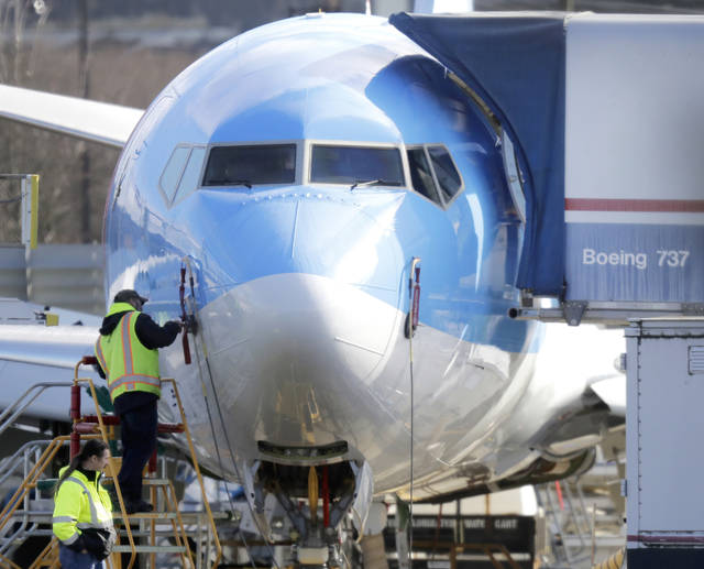 In this March 13 photo a worker stands on a platform near a Boeing 737 MAX 8 airplane being built for TUI Group at Boeing Co.'s Renton Assembly Plant in Renton, Wash. Boeing is cutting production of its grounded Max airliner this month to focus on fixing flight-control software and getting the planes back in the air.  Ted S. Warren | AP file photo