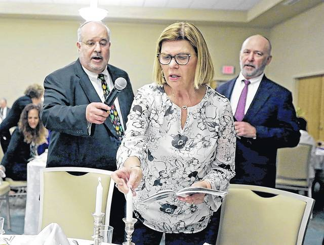 Rosemary Chromey, of Wilkes-Barre, center, says the Shehecheyanu as she lights the Passover seder candles with Rabbi Larry Kaplan, left, and Cantor Ahron Abraham at the Friedman Jewish Community Center in Kingston on Friday evening.  Bill Tarutis | For Times Leader
