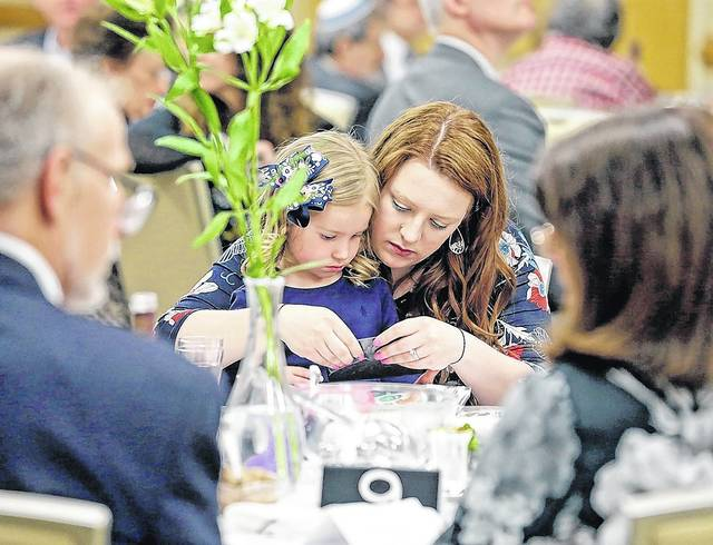 Four-year-old Avery Lantz and her mom Kiera, both of Kingston, open Passover stickers during the seder meal Friday evening at the Friedman Jewish Community Center in Kingston.	 Bill Tarutis | For Times Leader