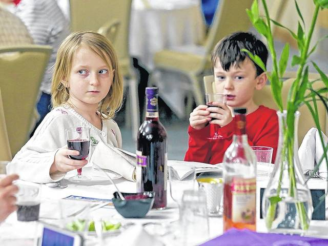 Andie Gray, 8, left, and her brother Kevin McCawley, 6, both of Sugarloaf Township, hold glasses of grape juice during the Passover seder at the Friedman Jewish Community Center in Kingston on Friday evening. Bill Tarutis | For Times Leader