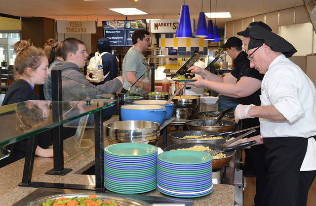 Paul Hill, right, a 15-year employee of Metz, works at the macaroni and cheese station during a recent lunch time at Misericordia University. Tony Callaio | For Times Leader