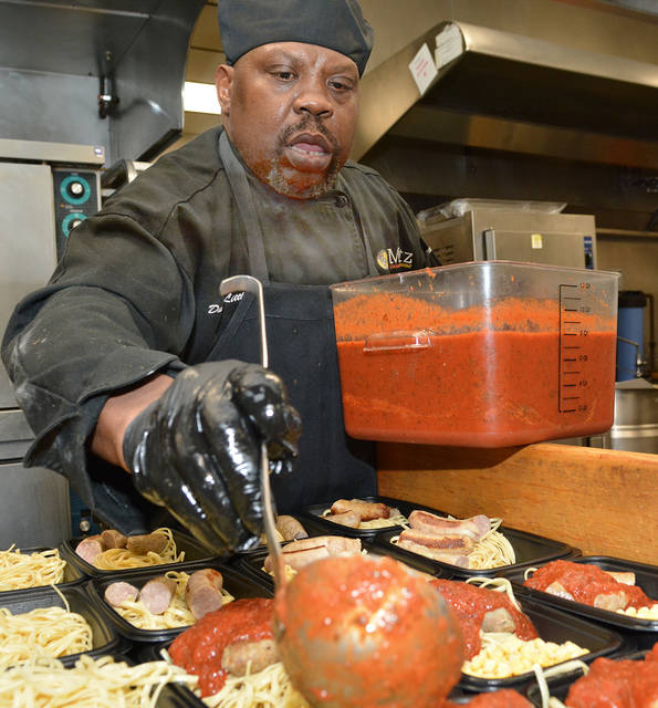 David Little, a 10-year Metz employee, tops pasta and sausage with tomato sauce as he prepares Meals For Kids, which The Metz Group donates to children in need in the Back Mountain, three times a week. Tony Callaio | For Times Leader