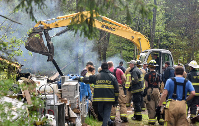 Firefighters watch as an excavator moves rubble at the site of an explosion in Dorrance Township on Friday.