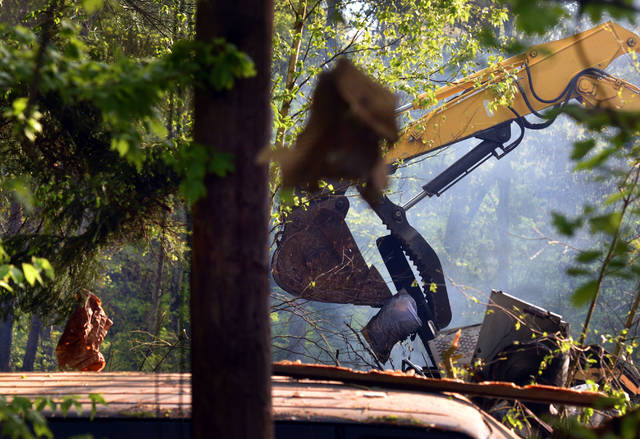 Debris hangs from trees as an excavator moves debis while looking for a missing man at a home explosion. State Police are investigating the home expolsion at 2165 Alberdeen Road in Dorrance Twp. PA. on Friday morning. One person is dead and another believed dead, an excavator has been brought in to search for a missing man, a 20 year old was  injured and taken to the hospital after the home was leveled at 1:40 am May 17, 2019. Aimee Dilger|Times Leader