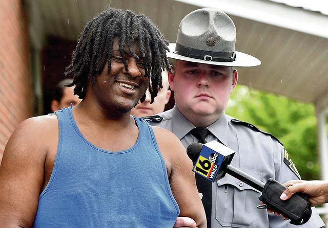 Homicide suspect Devin Malik Cunningham responds to reporters as he was led from district court on Tuesday where he was arraigned on homicide charges in connection with the April slaying of Joseph Monka, 71, in Edwardsville. Aimee Dilger | Times Leader