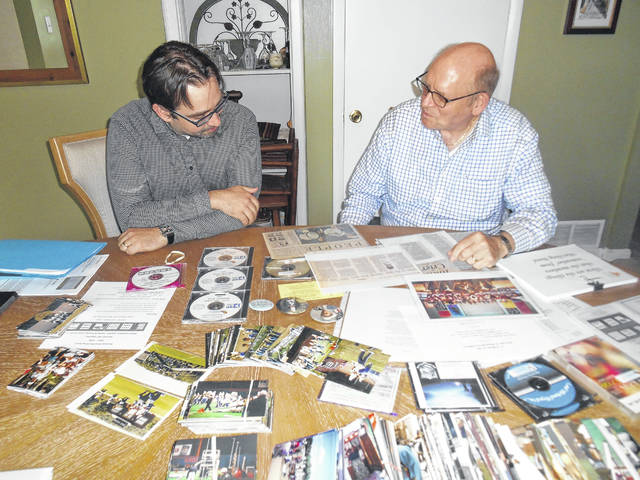 Hanover Area Marching Band alum Matthew Cannavale and his father, former Band Boosters president Ron Shandorf, look over memorabilia they will bring to a June 8 reunion, planned for members and friends of Hanover Area's award-winning marching band of the 1990s. Cannavale's sister, Andrea, and brother, Tony, are also alumni of the band. Mary Therese Biebel | Times Leader
