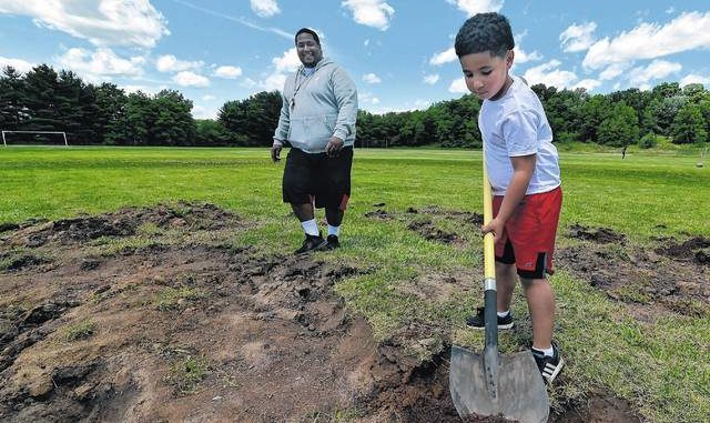 Volunteers transforming Coal Street baseball diamond into home base for football